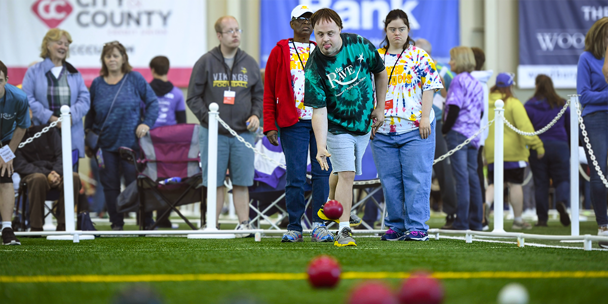 A Special Olympics Minnesota athlete rolls a bocce ball while his teammates and opponents look on